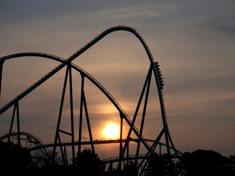 a rollercoaster descends down a large hill with the sunset in the background