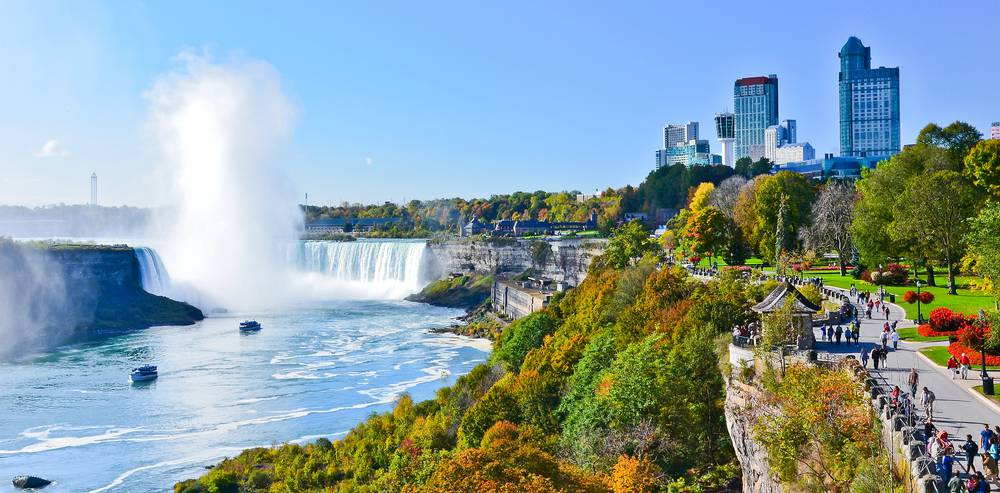 a view of niagara falls with tall buildings in the background